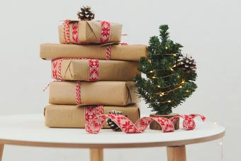 Stack of wrapped Christmas gifts next to a miniature Christmas tree