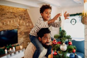 boy decorating Christmas tree with his father