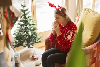 Women blowing her nose with allergies during holidays