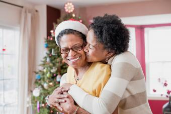 Mom and adult daughter hugging at Christmas tree