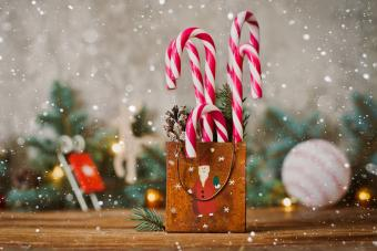 candy canes displayed in a vintage Christmas tin container