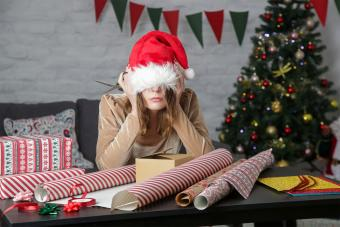 frustrated woman wrapping presents on Christmas Eve