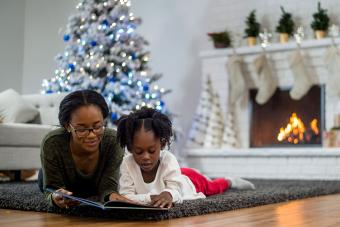 mother and daughter reading Christmas book together