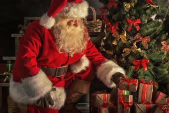 santa putting presents under tree