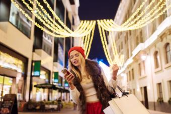 Young female shopper reading smartphone texts on street at xmas