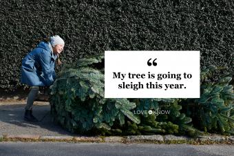 Girl pulling Christmas tree on footpath