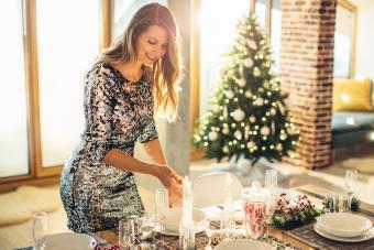 woman wearing metallic silver dress setting Christmas Eve table