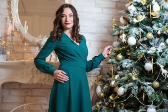 woman wearing green dress standing beside Christmas tree