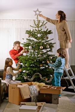 Family trimming Christmas tree