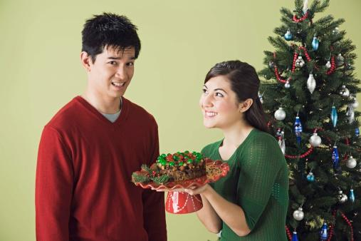 Woman giving man unwanted fruitcake