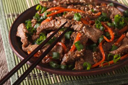Slices of beef fried with sesame seeds and carrots