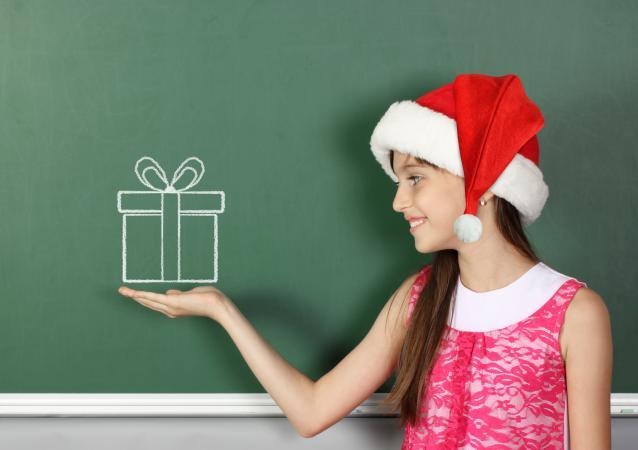 girl in Santa hat by chalkboard