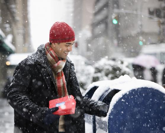 Bundled man mailing Christmas cards