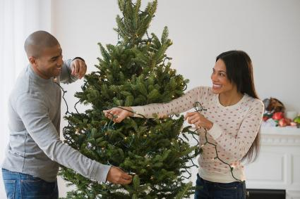 Couple placing string lights on Christmas tree