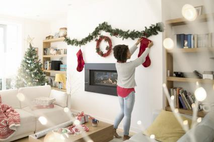 Woman hanging Christmas stockings above fireplace in living room