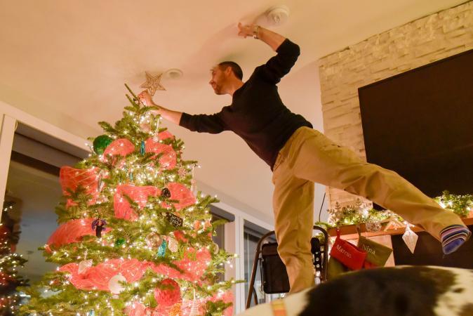 Man decorating Christmas tree at home