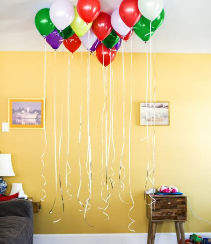Helium balloons with strings hanging down in living room