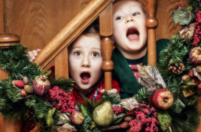 Children Looking through garland railing of stairs