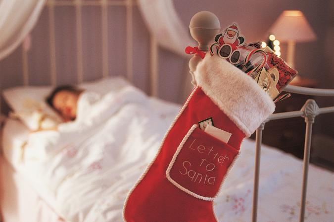 Christmas Stocking Hanging on a Bed Knob and a Child Sleeping in Bed