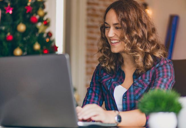 Woman on laptop writing Christmas newsletter
