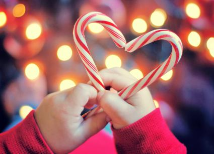 Child holding Christmas candy with heart shape