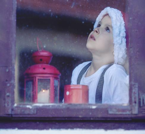 Child looking out snowy window at Christmastime.