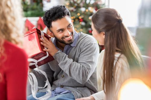 Man shaking Christmas gift at party