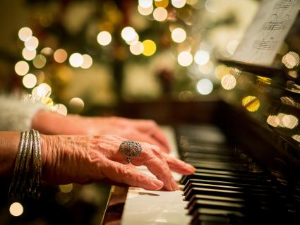 Woman playing Christmas carols on a piano