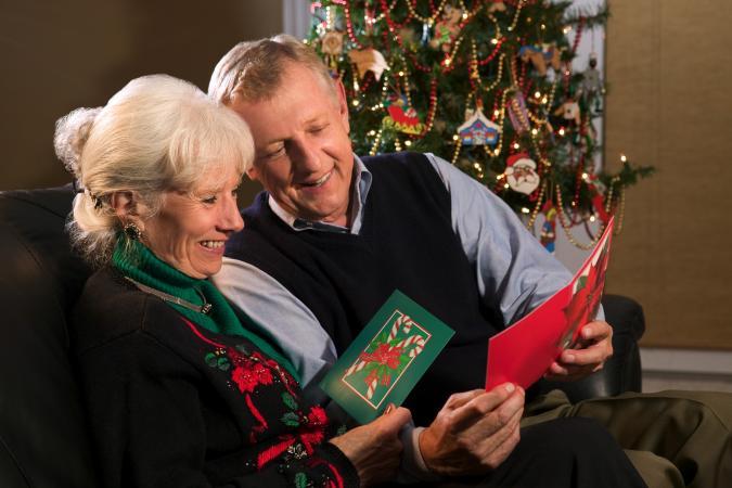 Couple enjoying reading Christmas greeting cards