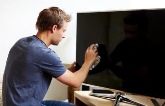 Man cleaning the screen of his smart TV
