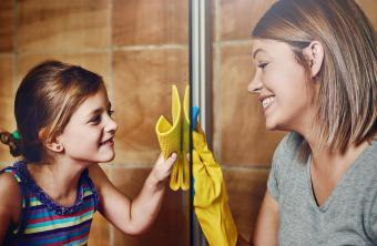 Mom and daughter cleaning glass shower