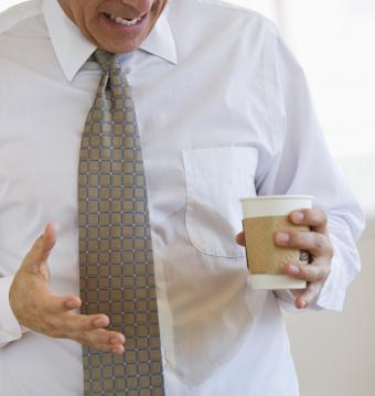 Businessman spilling coffee on shirt