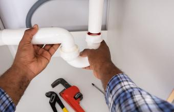 Plumber Fitting Sink Pipe In Kitchen