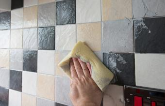 using a sponge to wipe of excess grout