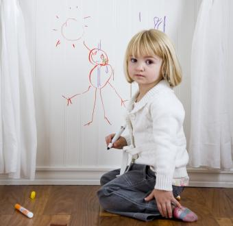 Child drawing on the wall with markers