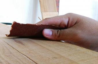 Man Using Sand Paper On Wood
