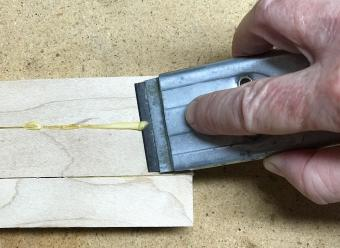 Scrape glue off wood with blade
