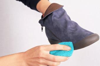 Woman cleaning Suede boots for winter care