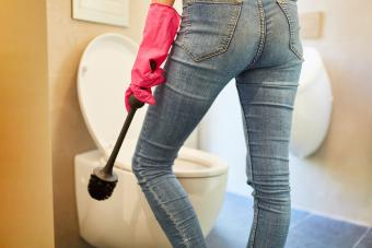 Woman cleaning a toilet