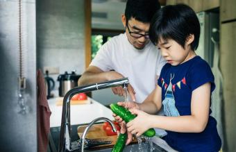 Father and son washing fresh fruit