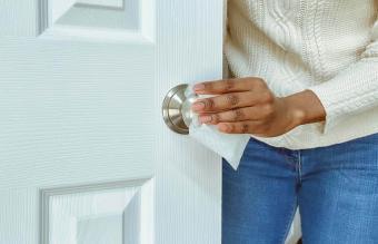 Woman Cleans Doorknob Using Disinfectant Wipe