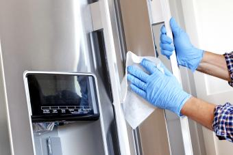 Man cleaning refrigerator with disinfectant wipe