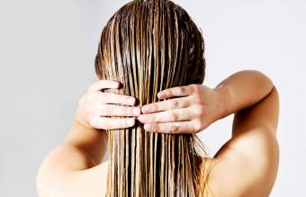 Woman applying conditioner on hair
