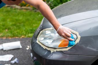 Man cleaning car headlights taped to protect paint rubbing with blue shop towel
