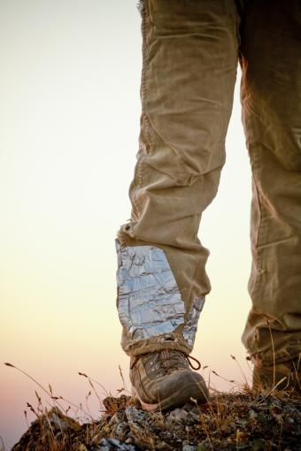 A hikers tattered pant leg fixed with duct tape