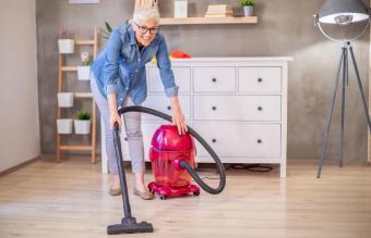 housewife vacuuming laminate floor