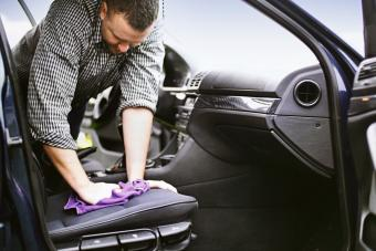 Man cleaning upholstery of his car