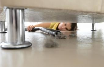 Woman vacuum under the sofa
