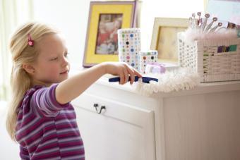 Little girl dusting dresser