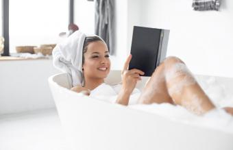Woman reading book in bathroom